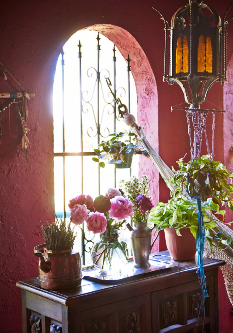 Wrought iron window in country house with flowers.