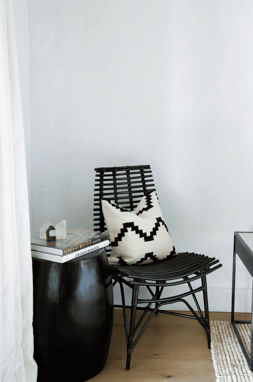 A corner filled with a black accent chair and a black side table