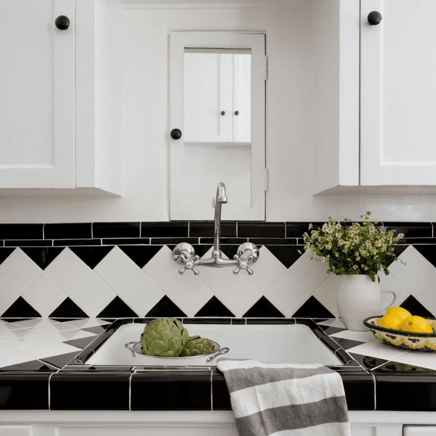 An all-white kitchen with a black and white tiled backsplash
