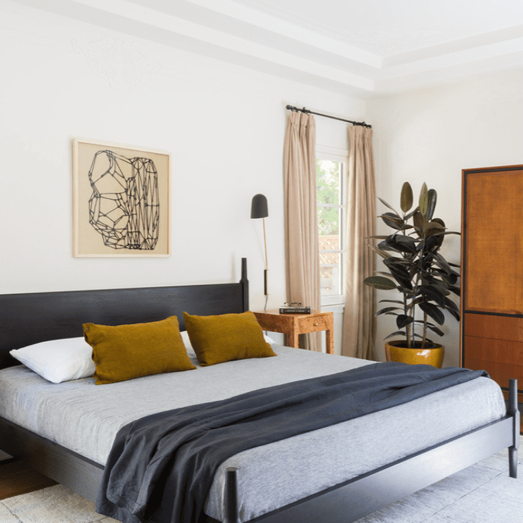 A midcentury modern bedroom with a bold bed, antique armoire, and striking overhead lighting