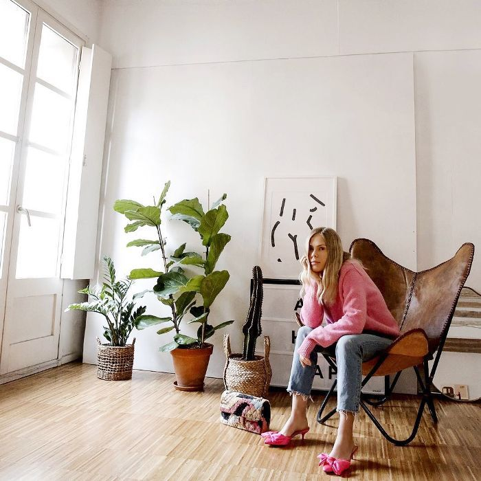 Woman sitting in a bright living room next to house plants