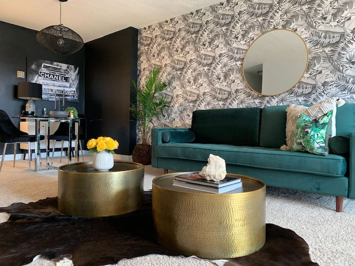 modern living room with teal couch, white and black fern pattern accent wall, two gold circular coffee tables