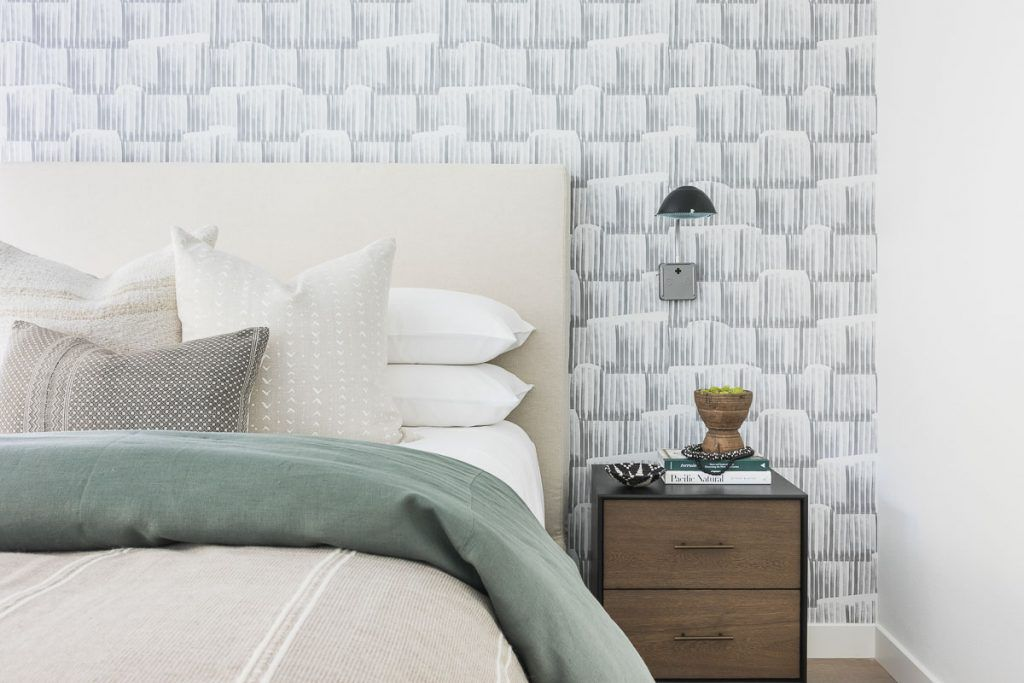 Soft neutral bed with printed wallpaper.