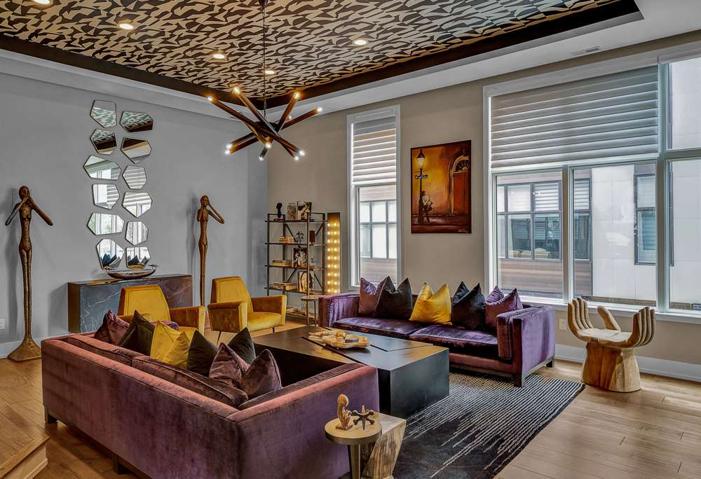 Living room with purple velvet sofas and yellow accent pillows and chairs