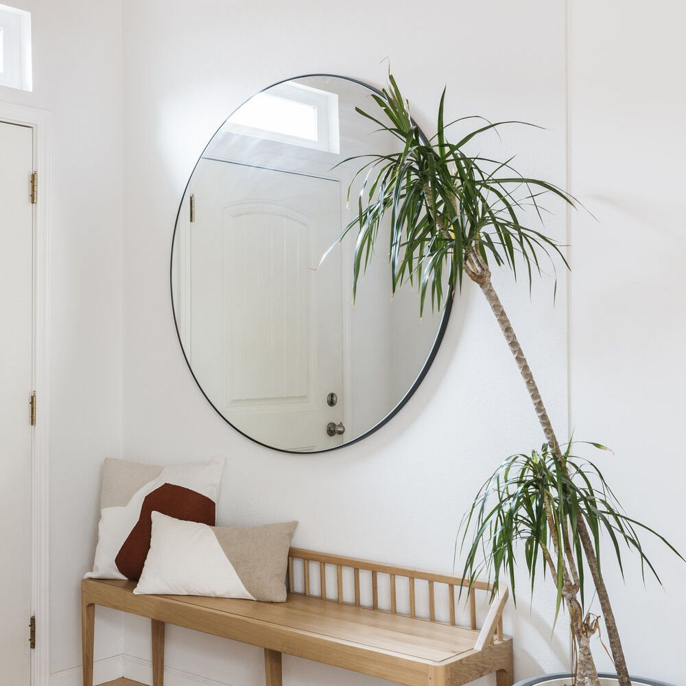 Entryway features large round mirror, wooden bench, potted plant