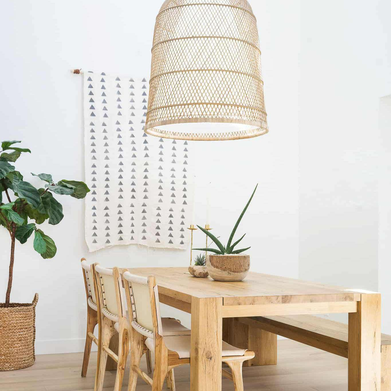 A dining room with a wooden table and a massive woven chandelier