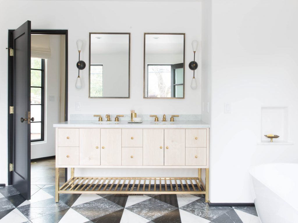 A bathroom with a wooden double vanity and metal-rimmed mirrors