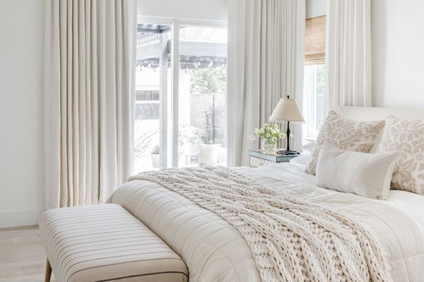 All white and beige bedroom with blackout curtains.