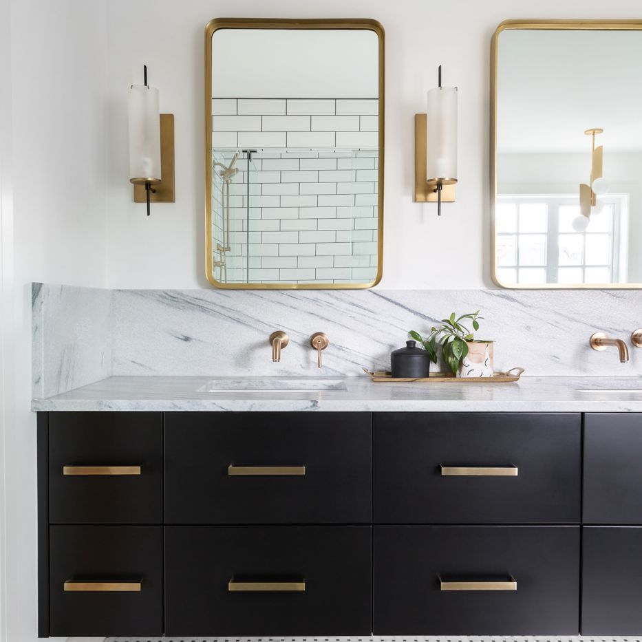 A double vanity with black cabinets and gold-rimmed mirrors