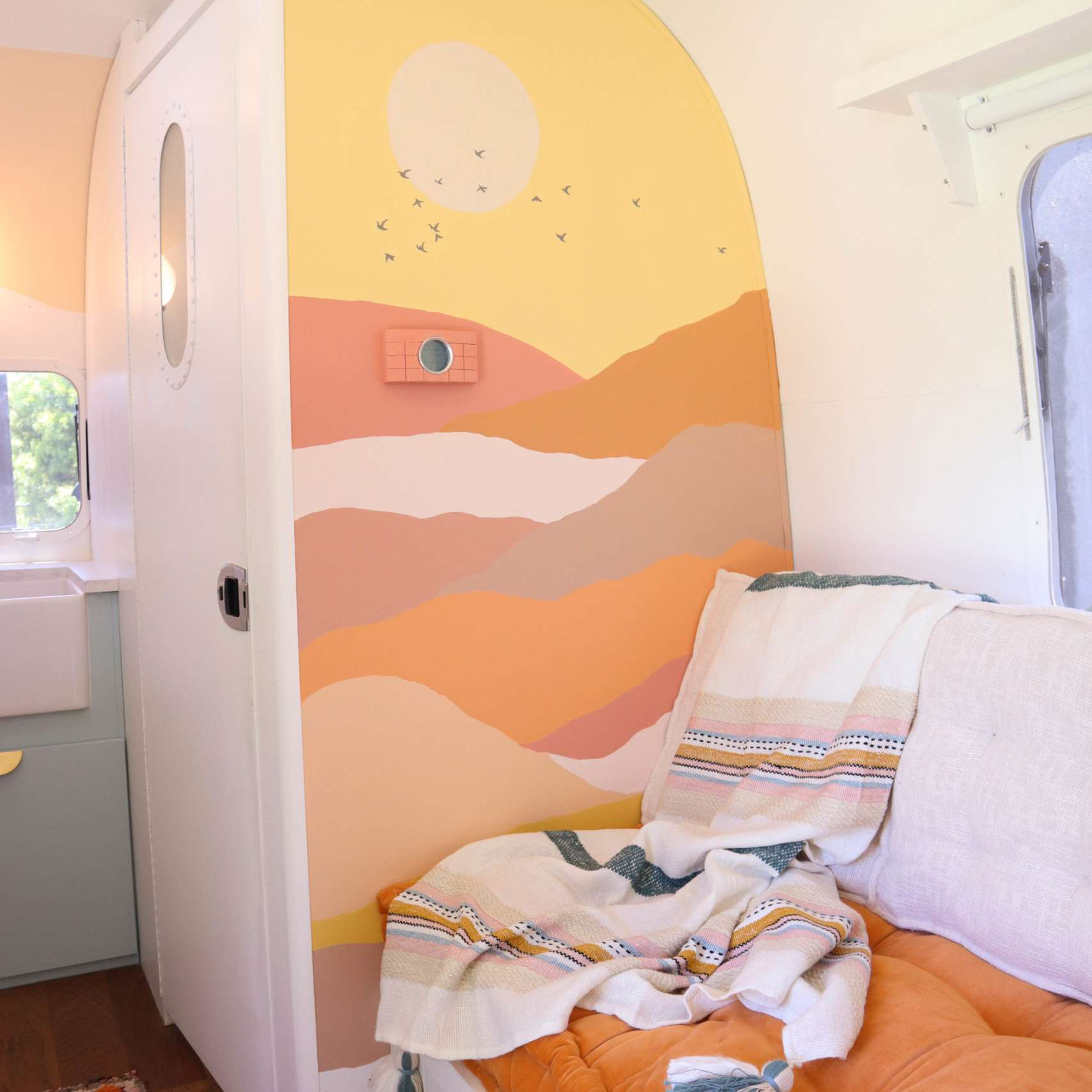 Mural wall of sunset and soft couch.
