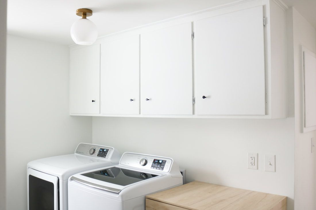 Laundry room with top loading washing machine.