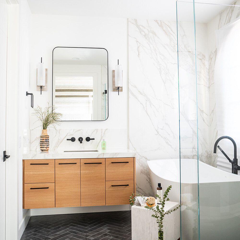 Bathroom with marble backsplash, floating vanity, dark chevron pattern tile flooring
