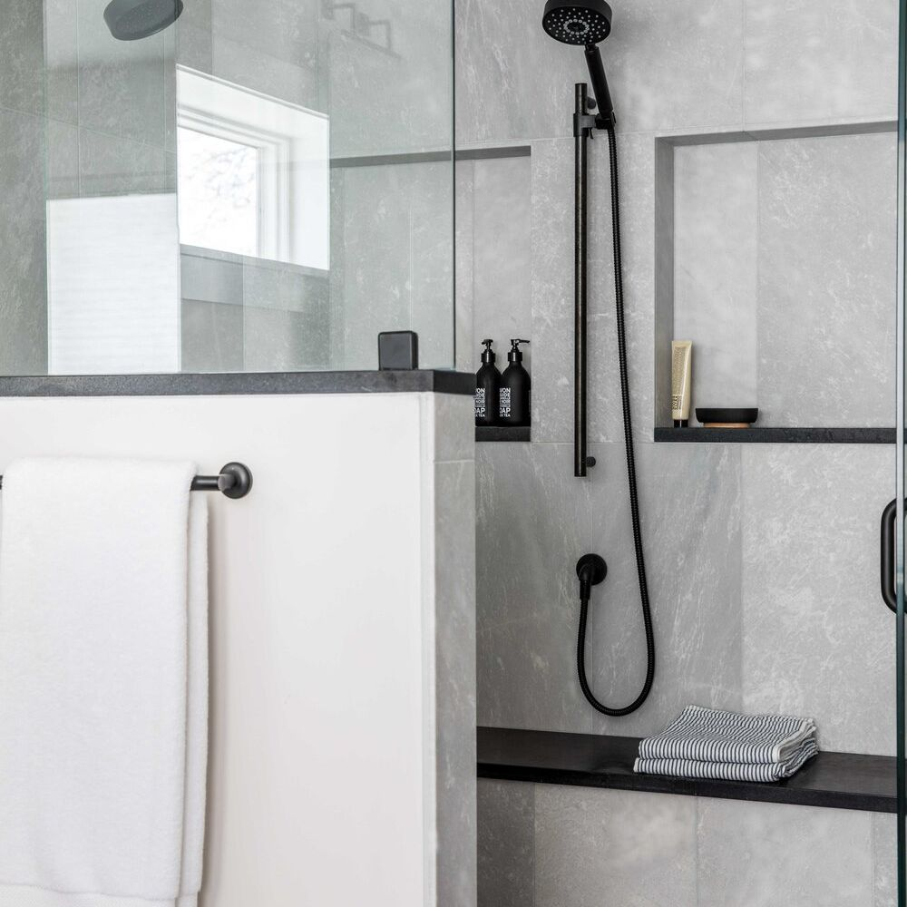 A cement-lined shower with black fixtures