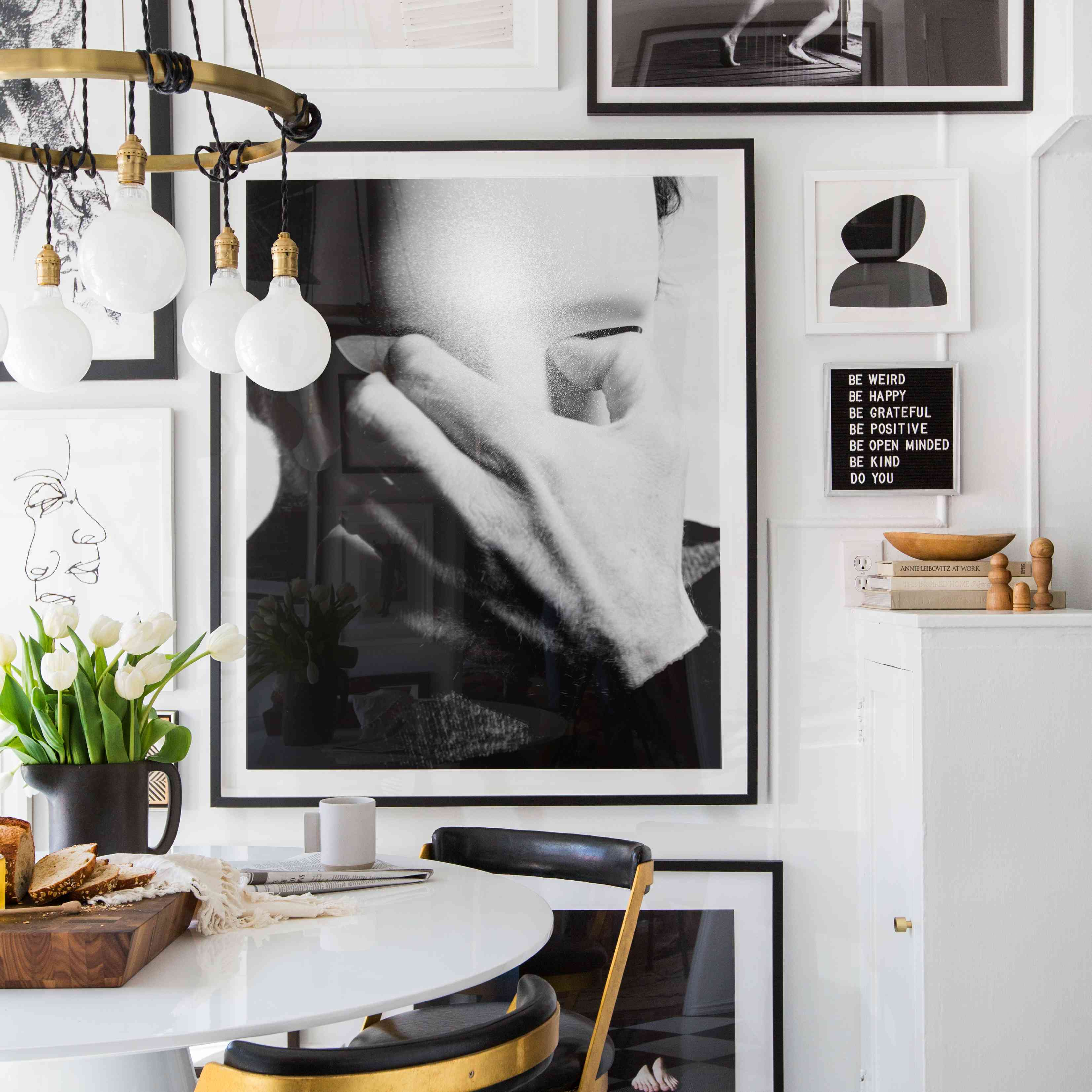 dining area with floor to ceiling black and white gallery wall