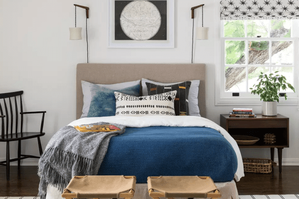 A bedroom with many storage solutions, including a nightstand, a basket, and two luggage racks (which have been placed at the foot of the bed)