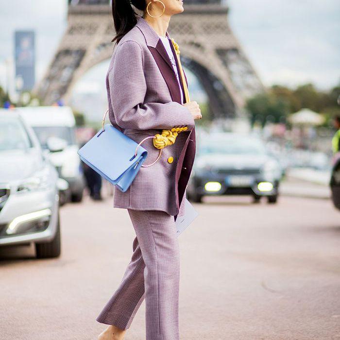 una mujer en traje pantalón lavanda y zapatos llamativos