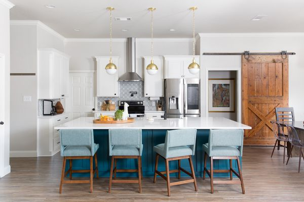 Bright kitchen with blue island and chairs.
