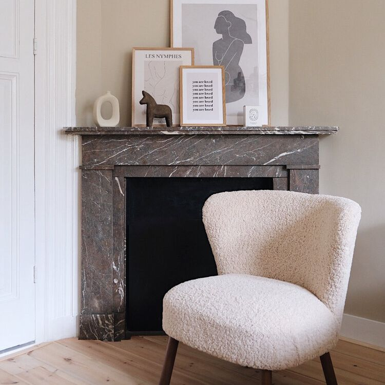 unused fireplace with pictures laying upon the mantel