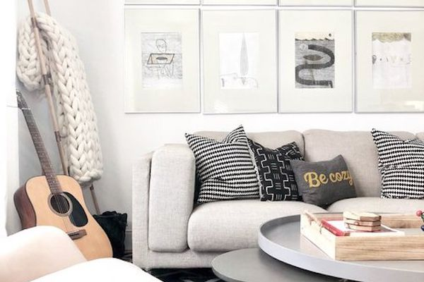 Cozy couch with knit blanket and guitar.