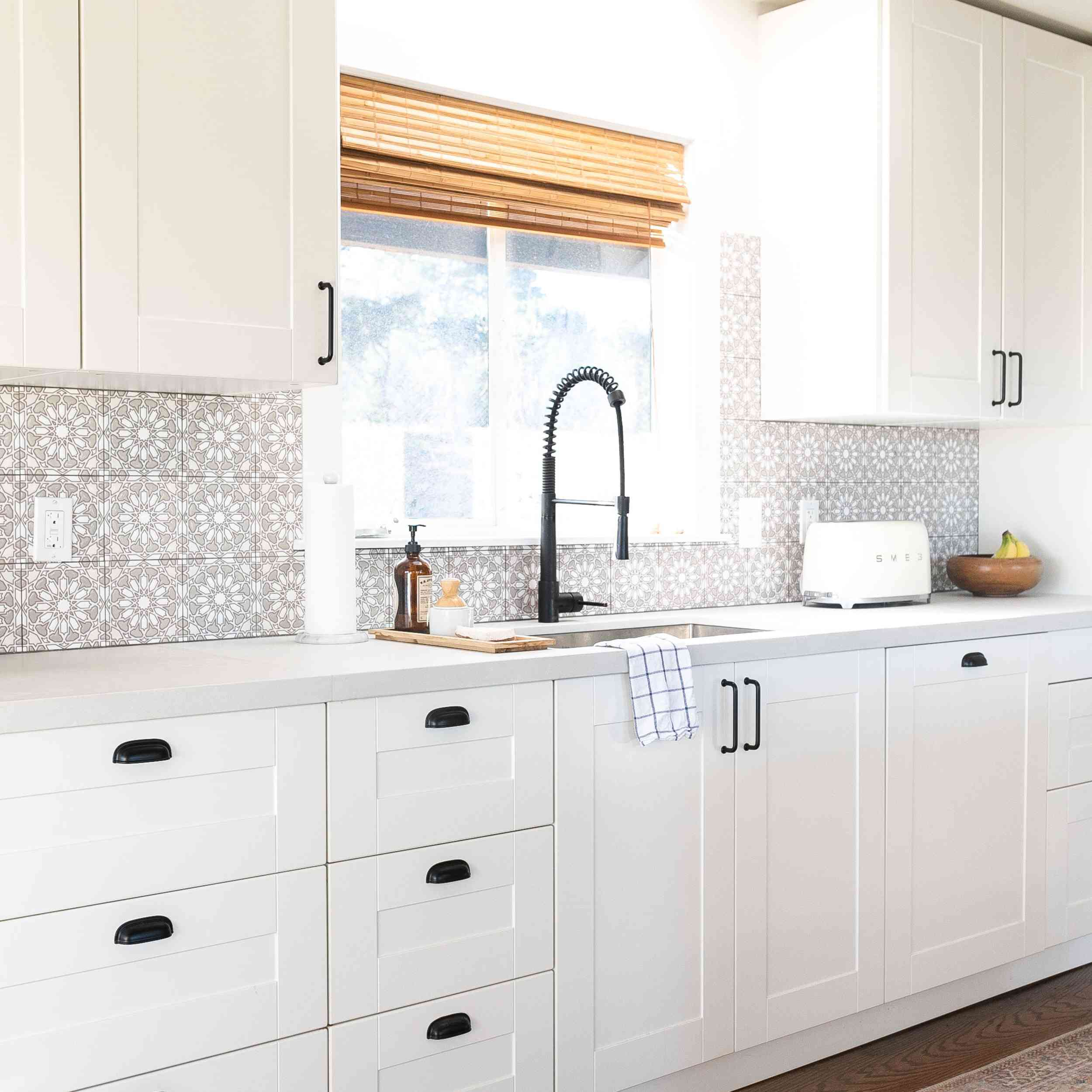 A kitchen with IKEA cabinets and a printed backsplash