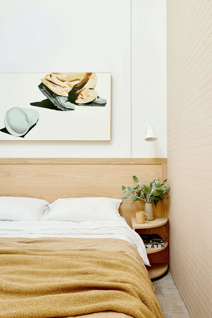 A bold, hyperreal hanging wall art matches the warm colors of the bedspread and headboard