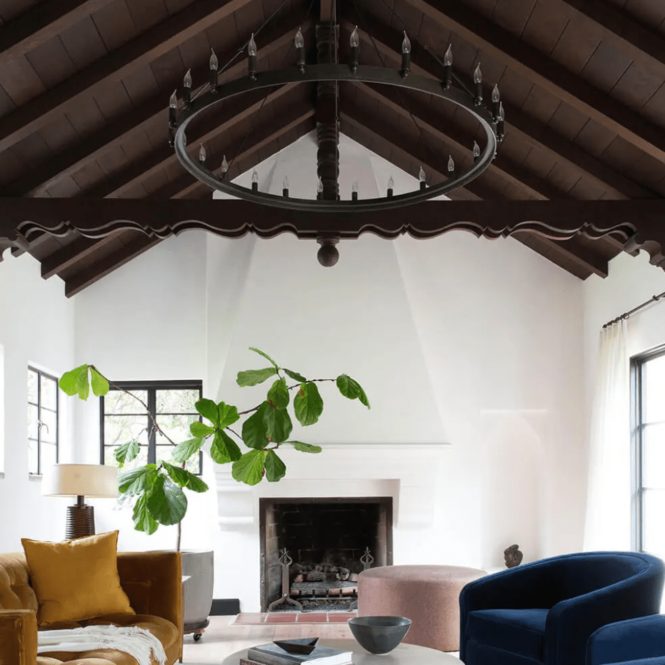 A living room with navy and gold furniture, a black chandelier, and a vaulted wood-lined ceiling