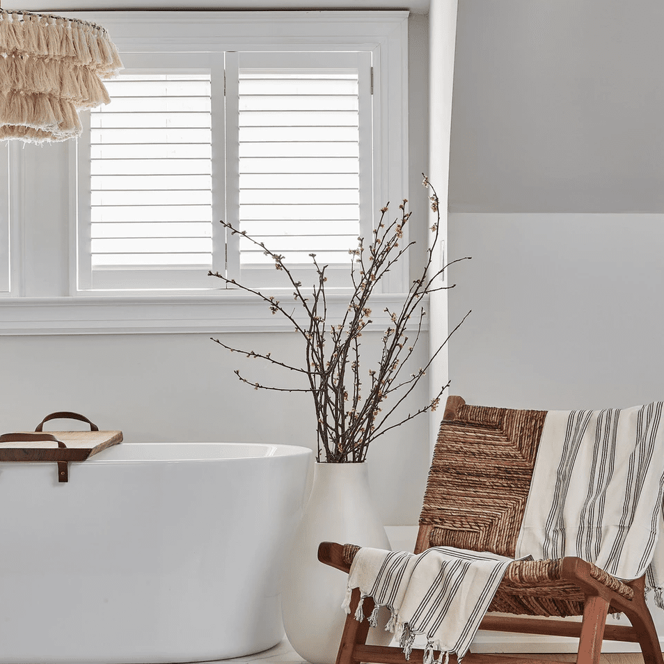 A white bathroom with a woven lounge chair in it