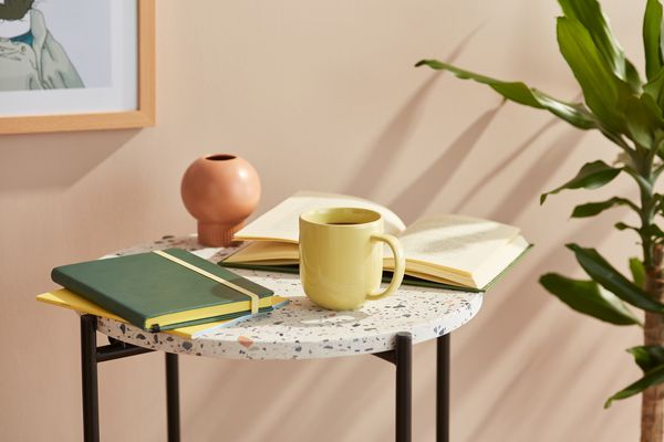 Still life of pale yellow mug of coffee with notebook and open book on round marble table.