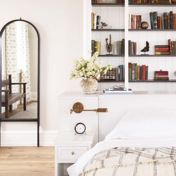 oval mirror and book shelves above a bed