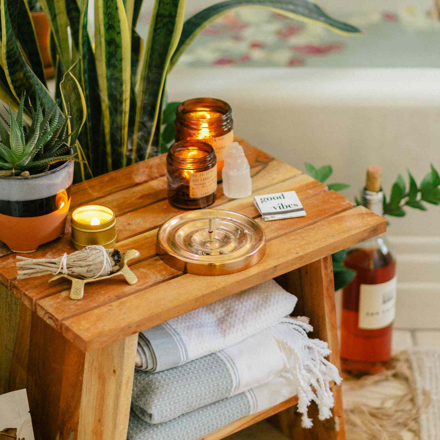 Boho styled bath table with candles, plants, and incense
