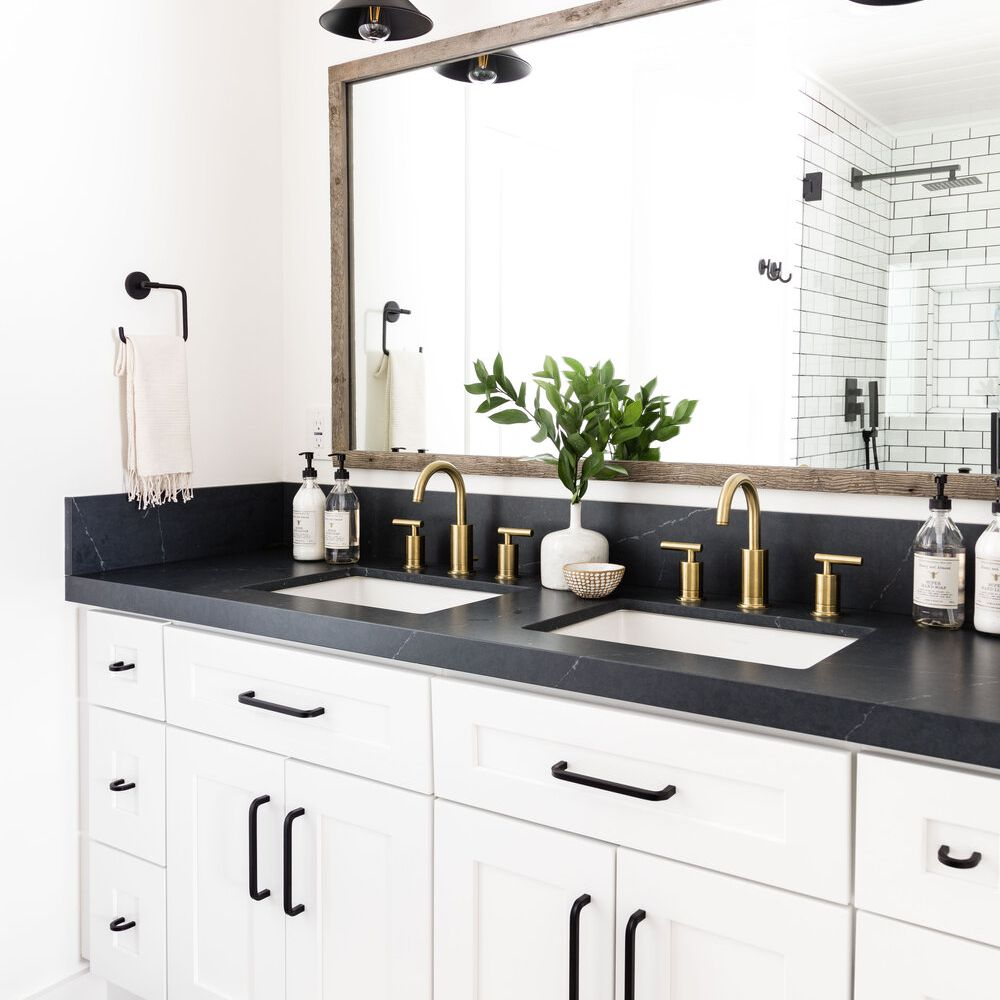 A bathroom with a black marble backsplash and matching hardware