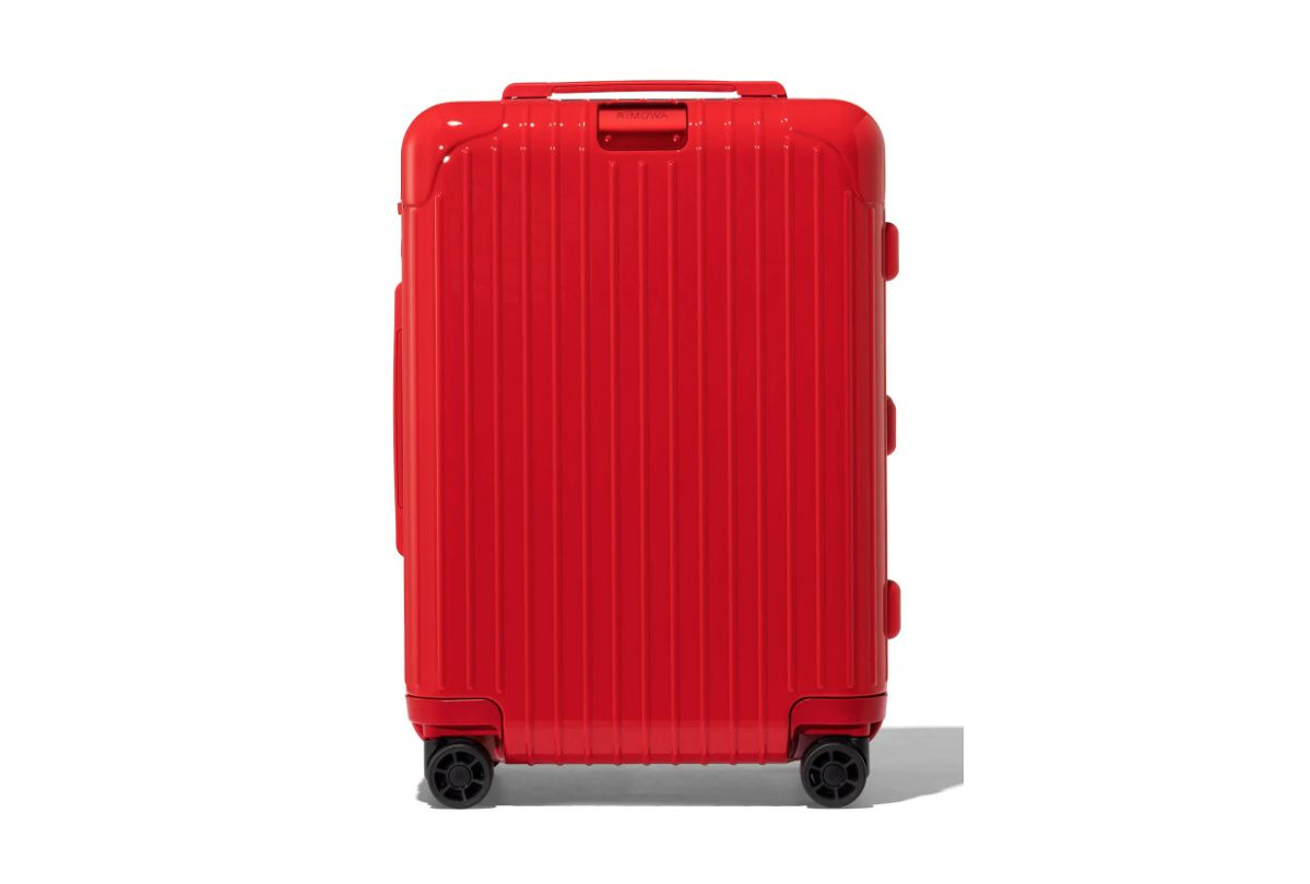 A red rolling spinner suitcase.