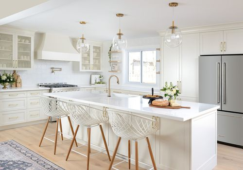 White and bright kitchen with light wood flooring.