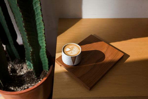 A cafe late with love heart art sits on a wooden board next to a cactus