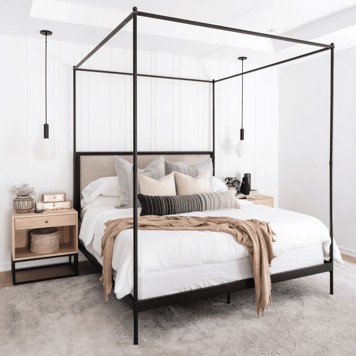 A minimalist bedroom with two industrial pendant lights