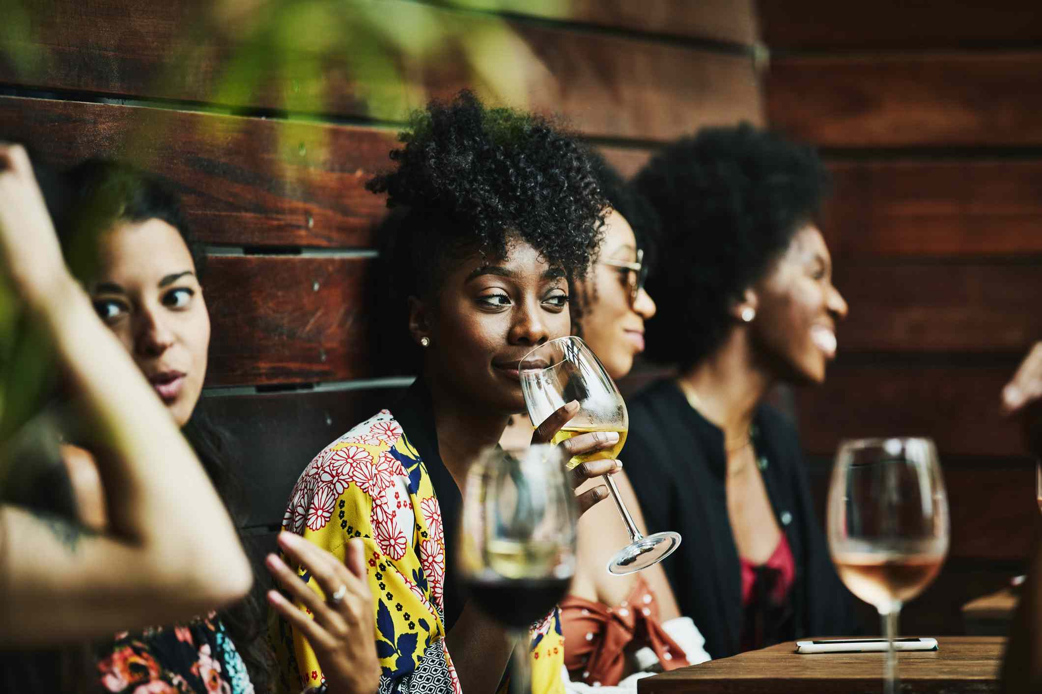 Young woman gather at table with glasses of wine and conversing