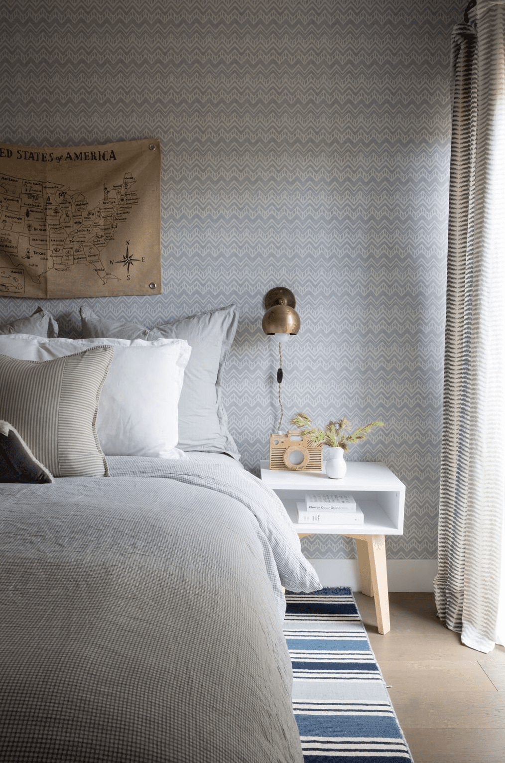 A bedroom with printed wallpaper and complementary printed curtains