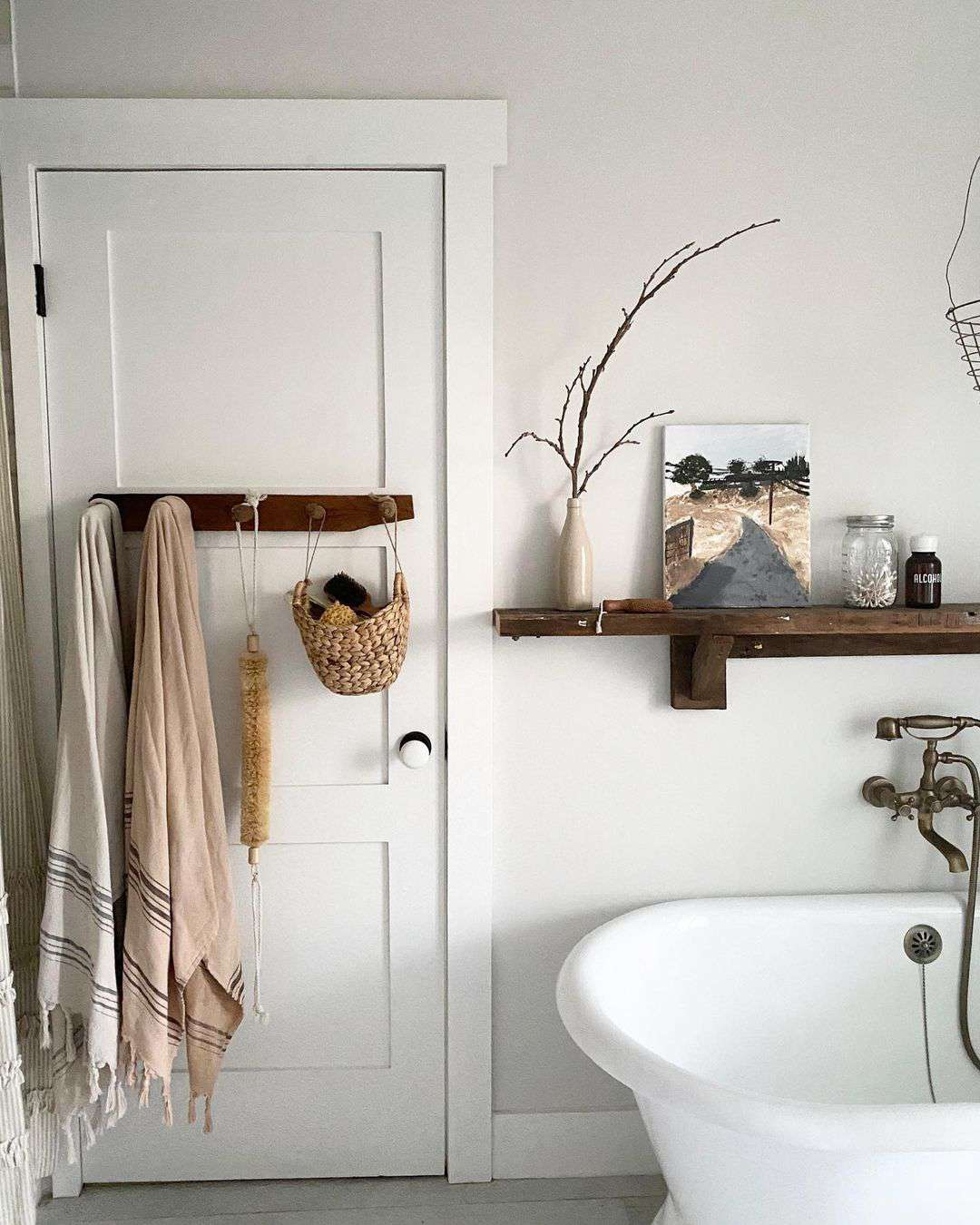 freestanding tub with shelf above and historic door nearby