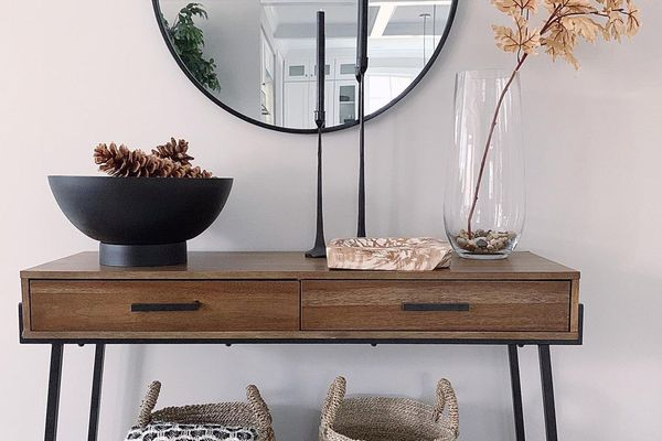 Entryway table with neutral decor and black taper candles.