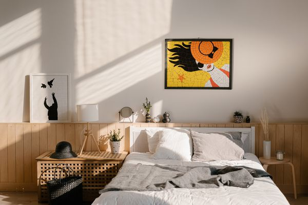 Colorful mosaic hanging over comfortable bed in cozy light bedroom in modern apartment