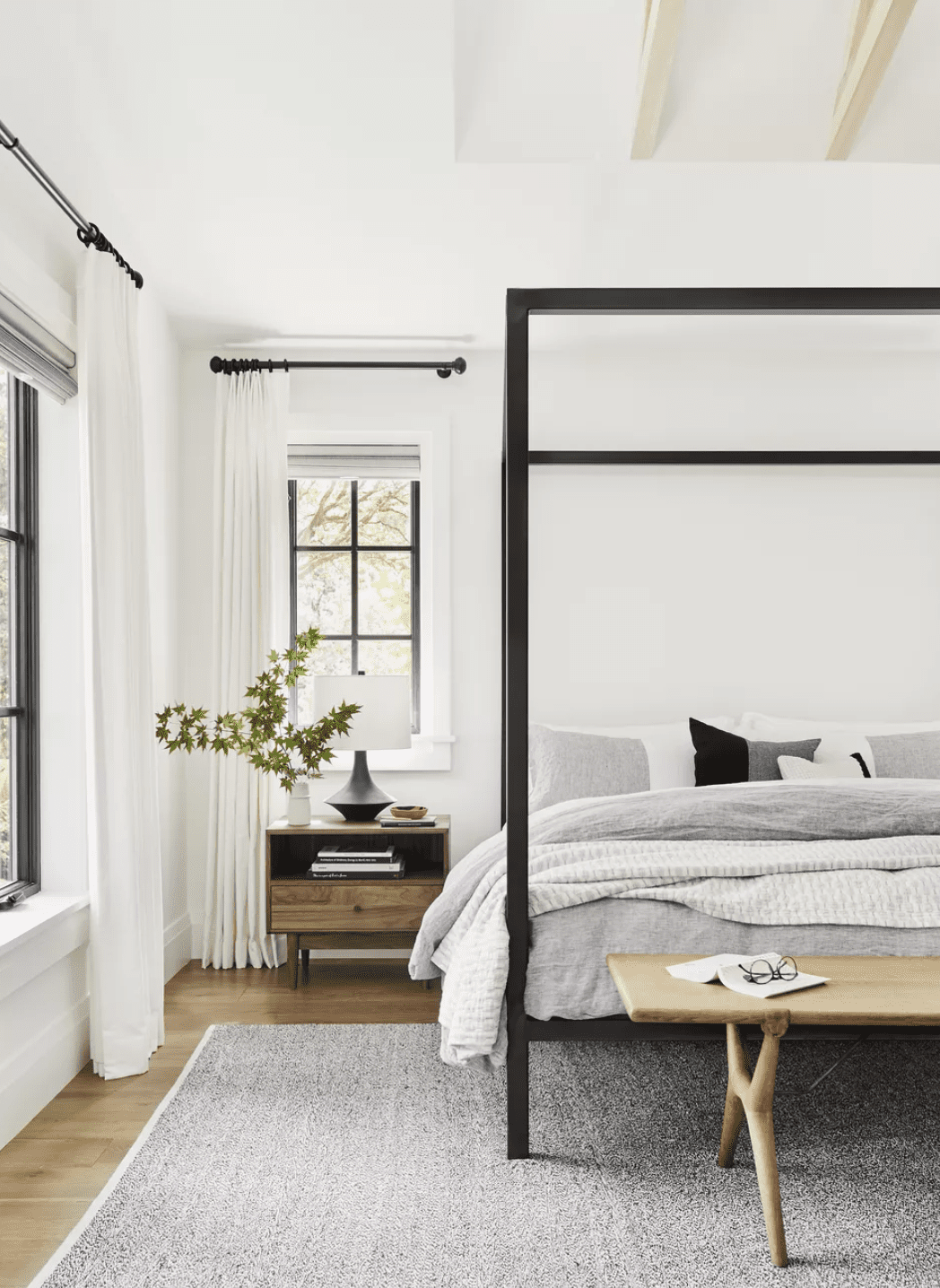 Zen bedroom with black and white tones, a four post bed, and light floor to ceiling curtains
