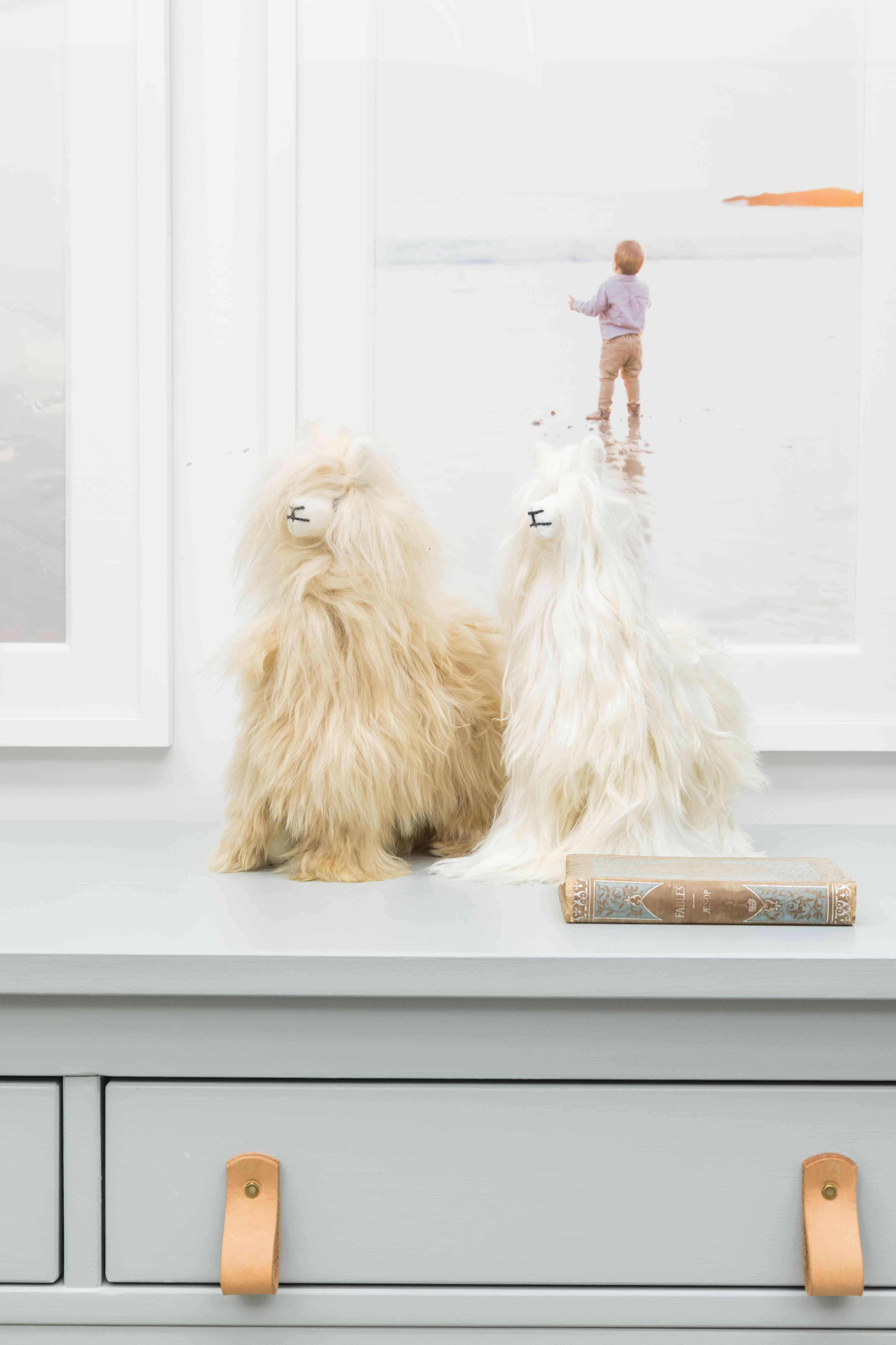 Two llama stuffed animals on dresser.