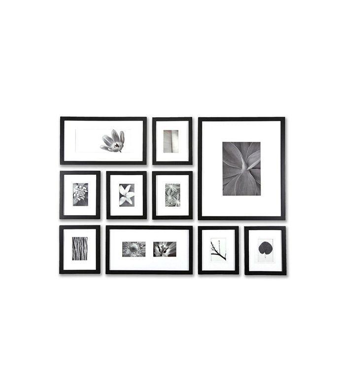 Una serie de fotos en blanco y negro enmarcadas en marcos negros colgaban al estilo de una galería.