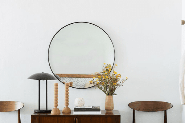 A wooden console table topped with minimal geometric decor and placed near a sleek circular mirror