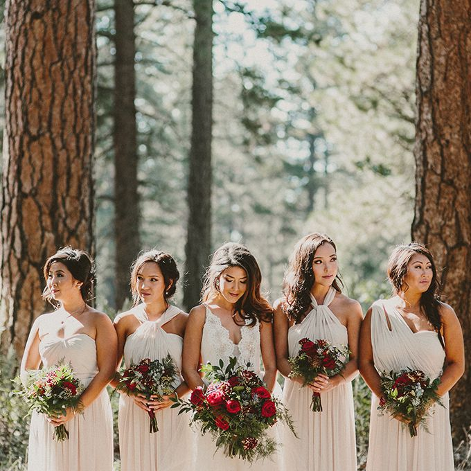 Four bridesmaids and one bride posing for a forrest wedding.
