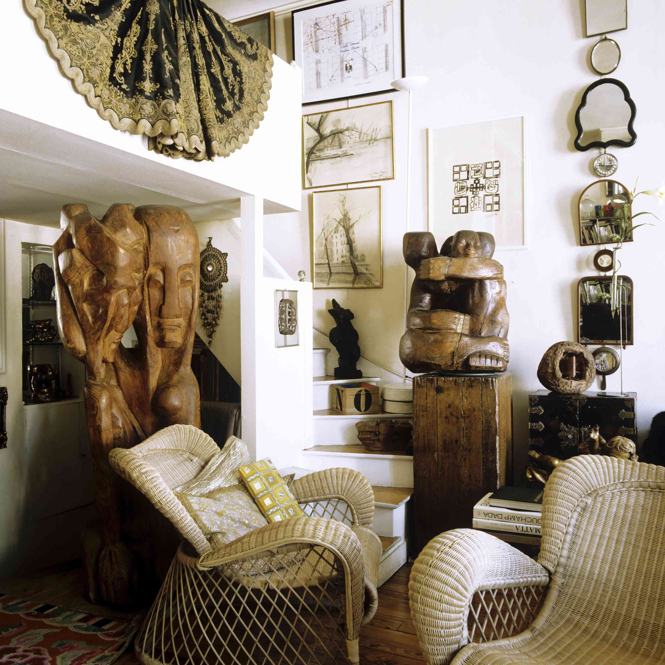 An eclectic living area with an impressive collection of artwork including several largescale wooden sculptures.