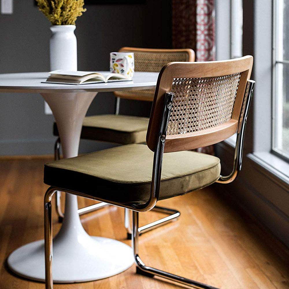 Two midcentury rattan and velvet dining chairs.