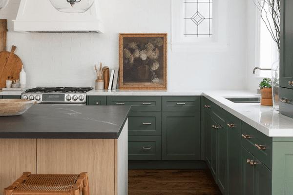 An elegant kitchen with dark green cabinets