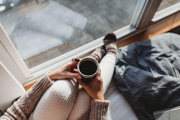 woman with coffee by a window