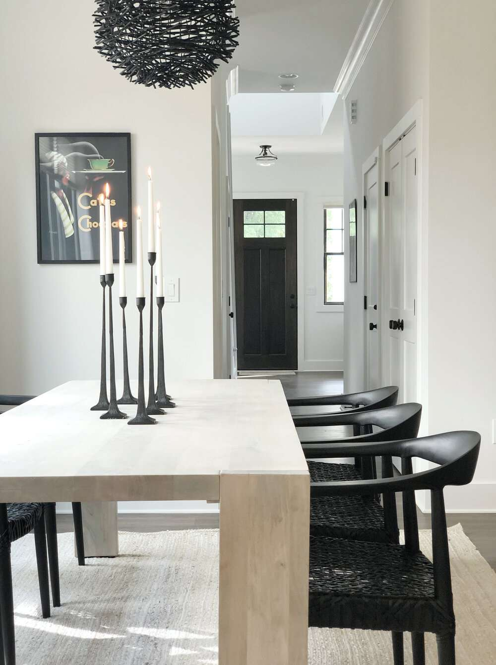 Modern dining room with a black front door in the background